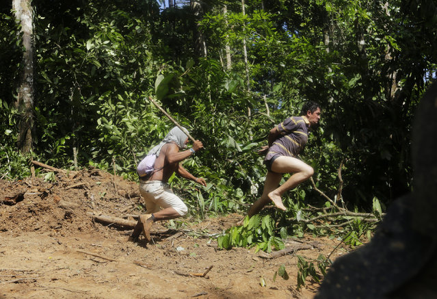 A Ka'apor Indian warrior (L) chases a logger who tried to escape after they captured him during a jungle expedition to search for and expel loggers from the Alto Turiacu Indian territory, near the Centro do Guilherme municipality in the northeast of Maranhao state in the Amazon basin, August 7, 2014. (Photo by Lunae Parracho/Reuters)