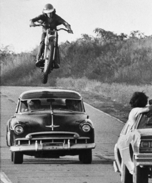 "Stunt cycle rider John Mulber leaps over a moving car during a chase scene of the movie production of ""Stingray"" which is being shot in the St. Louis area, August 22, 1977. The production, a spoof on other cops and robbers stunt filled chases, is due for release in early 1978. The jump is being filmed from the car in right foreground. (Photo by AP Photo)"