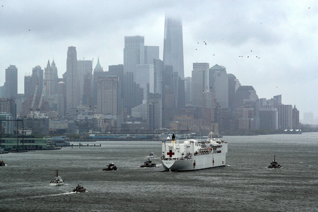 The U.S. Navy hospital ship USNS Comfort heads past lower Manhattan and the World Trade Center building under heavy fog as it leaves to return to its home port of Norfolk, Virginia, after treating patients during the outbreak of coronavirus disease (COVID-19) in New York City New York, U.S., April 30, 2020. (Photo by Mike Segar/Reuters)