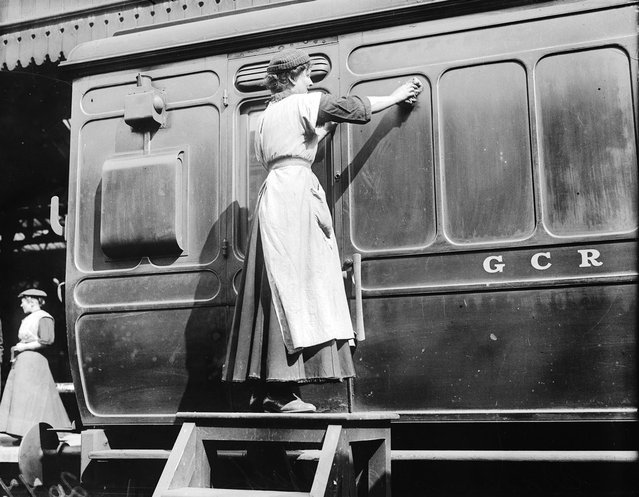A member of the Women Porters At Marylebone Station Group giving a Great Central Railways carriage a thorough clean, 1914. (Photo by Topical Press Agency)