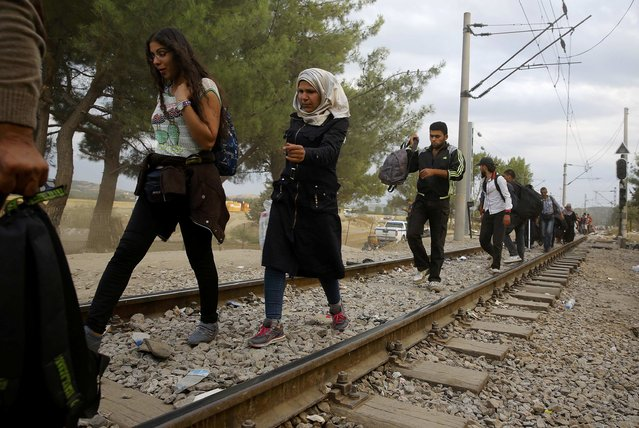 Syrian and Iraqi refugees walk along rail tracks on their way to cross Greece's border with Macedonia, near the Greek village of Idomeni, September 7, 2015. (Photo by Yannis Behrakis/Reuters)