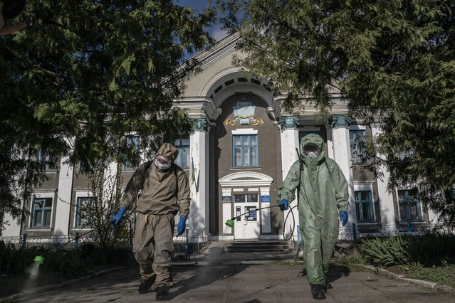 In this photo taken on Friday, May 1, 2020, firefighters in special protective suits spray chlorine in front of a hospital in Pochaiv, Ukraine. (Photo by Evgeniy Maloletka/AP Photo)