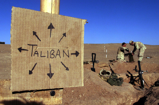 US Marines from Charlie 1/1 of the 15th MEU (Marine Expeditionary Unit) fill sand bags around their light mortar position on the front lines of the US Marine Corps base in southern Afghanistan December 1, 2001 nearby a cardboard sign reminding everyone that the Taliban forces could be anywhere and everywhere. This sign is one of several at an area that Charlie Company named Camp Justice on the perimiter of the larger base. (Photo by Jim Hollander/Reuters)