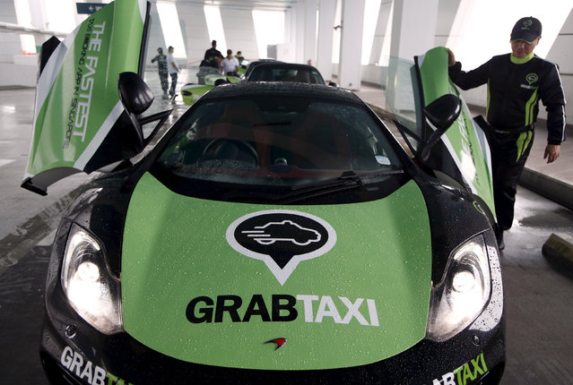 A driver checks his McLaren taxi after a photoshoot for taxi-booking app GrabTaxi's fleet of seven luxury cars in Singapore September 15, 2015. (Photo by Edgar Su/Reuters)