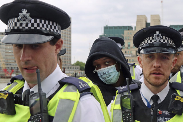 A protester is arrested during a Black Lives Matter protest rally on Vauxhall Bridge, in London, Sunday, June 7, 2020, in response to the recent killing of George Floyd by police officers in Minneapolis, USA, that has led to protests in many countries and across the US. (Photo by Gareth Fuller/PA Wire via AP Photo)