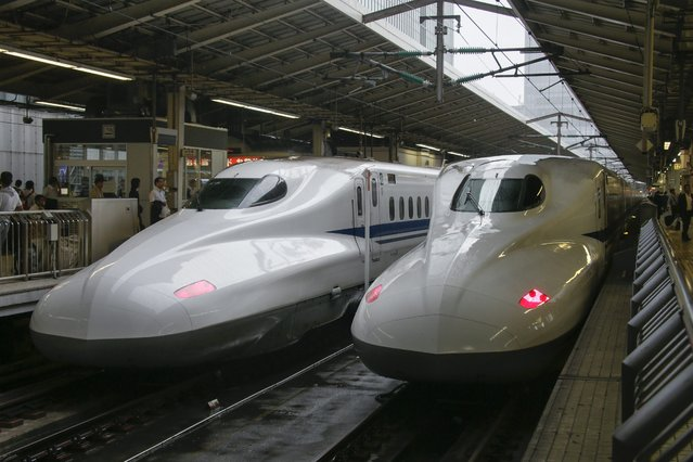 JR Tokai's Shinkansen bullet trains stand at platforms at Tokyo station in Tokyo, Japan, 01 October 2014, on the 50th anniversary of the high-speed train service. The Shinkansen is regarded as a symbol of the nation's economic boom, after its ignominious defeat and devastation in the World War II. The train went into service on 01 October 1964, just nine days before the opening of Tokyo Olympic Games. The bullet train debuted with a top speed of 210 km/h. (Photo by Kimimasa Mayama/EPA)