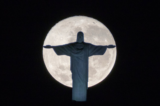 The silhouette of the statue of Christ the Redeemer atop Corcovado hill stands out against the full moon in Rio de Janeiro, Brazil, on July 19, 2016. (Photo by Yasuyoshi Chiba/AFP Photo)