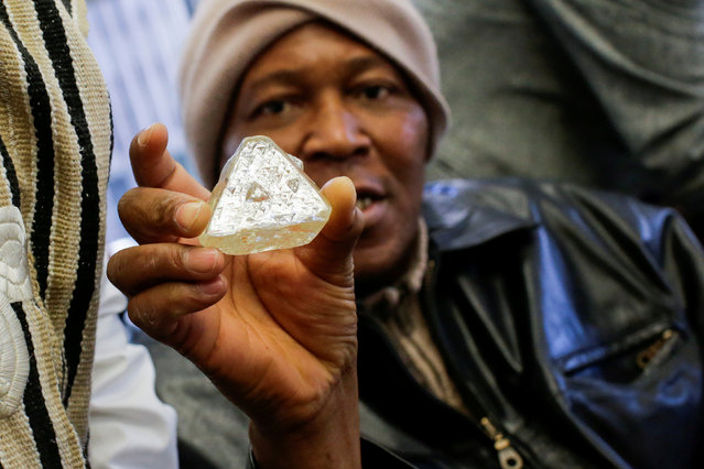 Dennis Kabatto, from Sierra Leone, holds the 709-carat diamond as it is presented during a news conference before auction in New York, U.S., November 21, 2017. (Photo by Eduardo Munoz/Reuters)