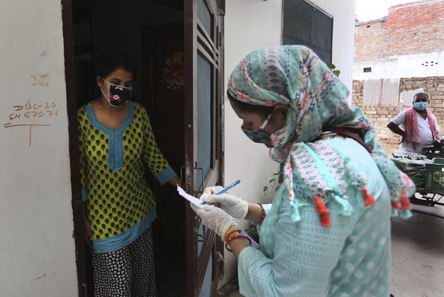 An Indian government school teacher writes down the details of a family during a survey at a residential neighborhood in New Delhi, India, Saturday, June 27, 2020. A massive survey to take down health details of New Delhi's entire population of 28 millions and test everyone with symptoms for COVID-19 started Saturday. Teams comprising of health workers and other government officials, including teachers went from home to home to conduct the survey, that is trying to screen everyone by July 6, as Delhi has become the worst hit city in India. (Photo by Manish Swarup/AP Photo)