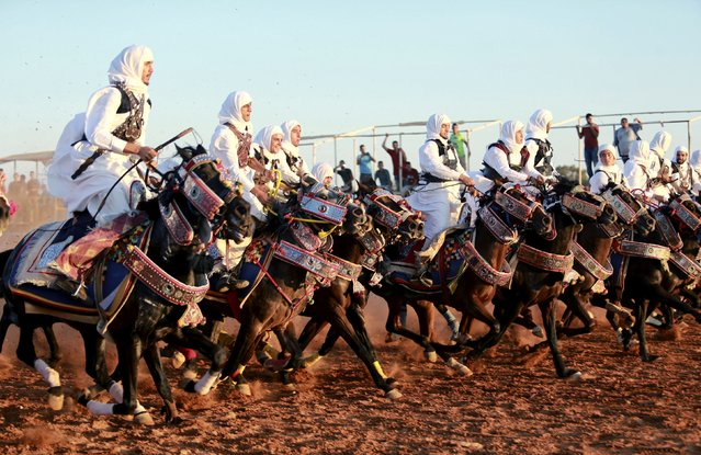 Horse riders dressed in traditional costumes participate in the annual Libyan equestrian festival, in Benghazi, Libya, on October 10, 2014. (Photo by Esam Omran Al-Fetori/Reuters)