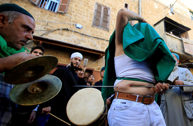 A member of a Lebanese Sufi Muslim group pushes a skewer through himself as part of annual Sufi ritual to commemorate the birth of Prophet Mohammed at the port city of Sidon, Lebanon November 30, 2017. (Photo by Ali Hashisho/Reuters)