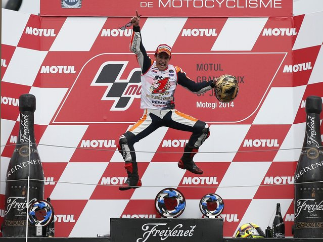 Honda MotoGP rider Marc Marquez of Spain jumps into the air on the podium after he finished in second place to become the 2014 world champion at the Japanese Grand Prix at the Twin Ring Motegi circuit in Motegi, north of Tokyo October 12, 2014. Spaniard Marc Marquez retained his MotoGP world title with a second place finish at his team Honda's home Motegi circuit in the Japanese Grand Prix on Sunday. (Photo by Toru Hanai/Reuters)