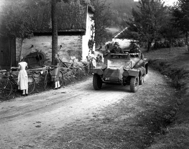 Watched by young Czech women with bicycles a German armoured car drives through Waldhaeus in Czechoslovakia, an invasion which led up to WWII. 3rd October 1938. (Photo by Keystone)
