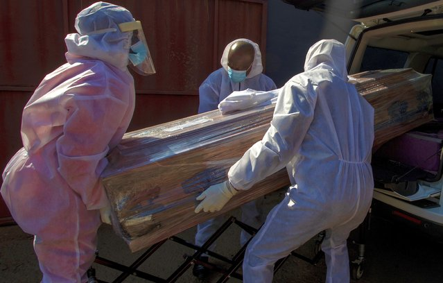 Funeral home workers in protective suits carry the coffin of a woman who died from COVID-19 into a hearse in Katlehong, near Johannesburg, South Africa, Tuesday, July 21, 2020. South Africa, last Saturday became one of the top five worst-hit countries in the coronavirus pandemic, as breathtaking new infection numbers around the world were a reminder that a return to normal life is still far from sight. (Photo by Themba Hadebe/AP Photo)