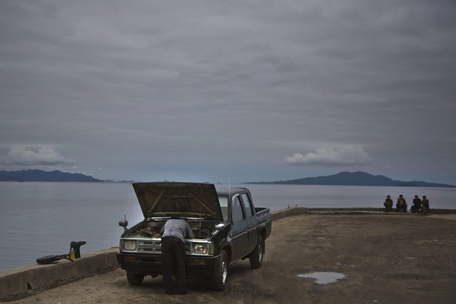 In this June 21, 2014 photo, a man works on his car as others sit next to the sea Wonsan, North Korea. (Photo by David Guttenfelder/AP Photo)