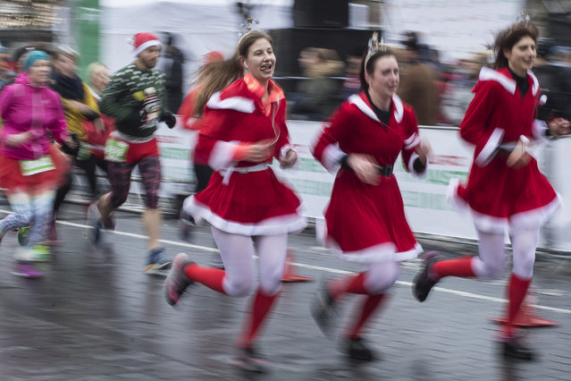 Girls take part in the traditional seasonal Christmas run along the streets of Vilnius, Lithuania, Sunday, December 17, 2017. The festive run attracts many hundreds of people to the capital dressed as Santa Clause to take part in the sporting event. (Photo by Mindaugas Kulbis/AP Photo)
