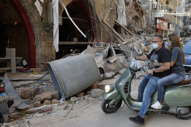 A couple drives past destruction after a massive explosion in Beirut, Lebanon, Wednesday, August 5, 2020. The explosion flattened much of a port and damaged buildings across Beirut, sending a giant mushroom cloud into the sky. In addition to those who died, more than 3,000 other people were injured, with bodies buried in the rubble, officials said. (Photo by Hassan Ammar/AP Photo)