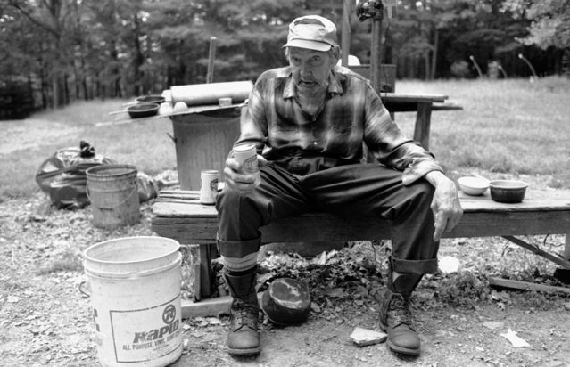 """Pat Rupert, 76, sits outside his Sheffield, Pennsylvania shed on October 20, 1982, fresh snuff in his lip and a cold beer in one hand. He and his older brother live in a disheveled corrugated iron box that once housed a large gasoline engine. There is no refrigerator, telephone or running water inside. Rupert says, """"I know where I am and I know what I am"""". (Photo by Gene Puskar/AP Photo)"""