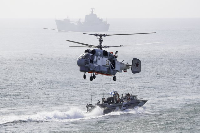 Russian navy ships and a helicopter take a part in a landing operation during military drills at the Black Sea coast, Crimea, Friday, September 9, 2016. (Photo by Pavel Golovkin/AP Photo)