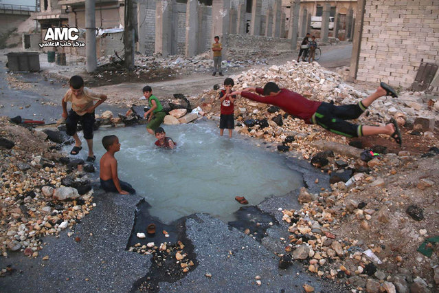 This Wednesday, August 31, 2016 photo, provided by the Syrian anti-government activist group Aleppo Media Center (AMC), shows Syrian boys dive into a hole filled with water that was caused by a missile attack in the rebel-held neighborhood of Sheikh Saeed in Aleppo province, Syria. (Photo by Aleppo Media Center via AP Photo)