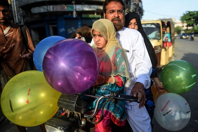 Children hold balloons after offering prayers with their father (C) during the Eid al-Adha, the feast of sacrifice, in Karachi on August 1, 2020. (Photo by Rizwan Tabassum/AFP Photo)