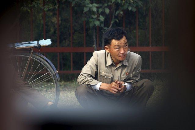 A man smokes a cigarette in downtown Pyongyang, North Korea October 8, 2015. (Photo by Damir Sagolj/Reuters)