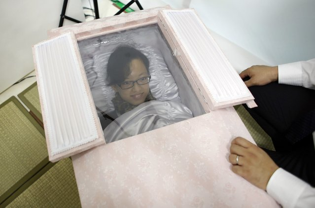 Natsumi Niki smiles as she lies in a coffin to test it during an end-of-life seminar held by Japan's largest retailer Aeon Co in Tokyo October 24, 2014. (Photo by Toru Hanai/Reuters)