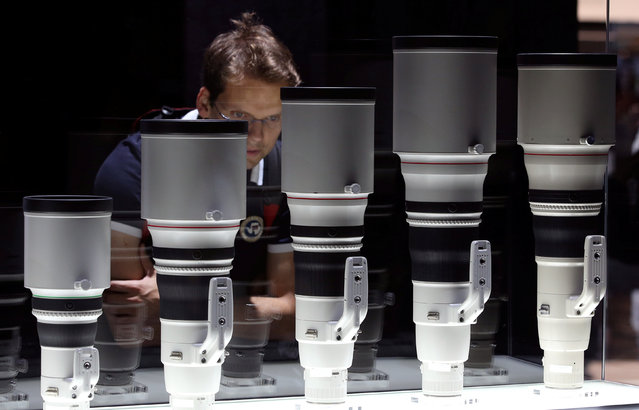 A visitor looks at telephoto lenses at the Canon booth on the Photokina, the world's largest fair for imaging in Cologne, Germany, September 20, 2016. (Photo by Fabrizio Bensch/Reuters)