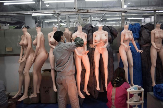 This photo taken on February 1, 2018 shows a worker preparing silicone dolls at a factory of EXDOLL, a firm based in the northeastern Chinese port city of Dalian. (Photo by Fred Dufour/AFP Photo)