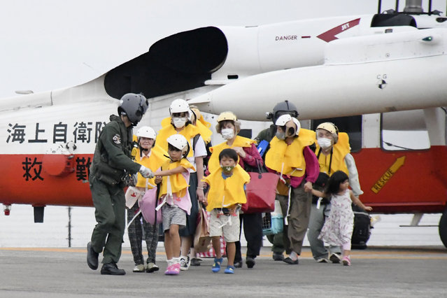 Residents of the islands arrive at a heliport in Kagoshima, southern Japan Friday, September 4, 2020 to take refuge ahead of a powerful typhoon. A powerful typhoon was barreling toward the southern cluster of Japanese Okinawa islands on Saturday, prompting warnings about torrential rainfall and fierce wind gusts. (Photo by Kyodo News via AP Photo)