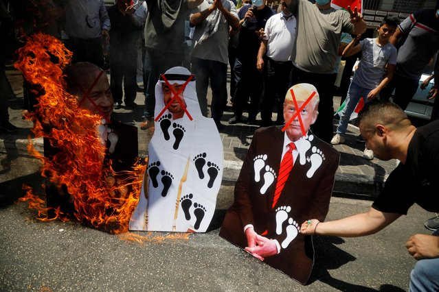 Palestinians burn cutouts depicting U.S. President Donald Trump and Abu Dhabi Crown Prince Mohammed bin Zayed al-Nahyan and Israeli Prime Minister Benjamin Netanyahu during a protest against the United Arab Emirates' deal with Israel to normalise relations, in Nablus in the Israeli-occupied West Bank on August 14, 2020. (Photo by Raneen Sawafta/Reuters)