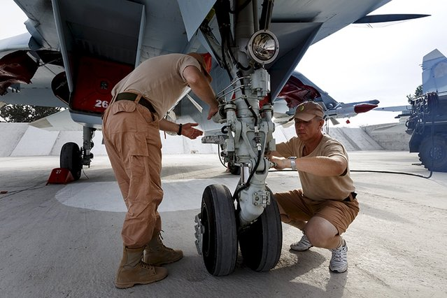 Russian ground staff members work on a Sukhoi Su-30 fighter jet at the Hmeymim air base near Latakia, Syria, in this handout photograph released by Russia's Defence Ministry October 22, 2015. (Photo by Reuters/Ministry of Defence of the Russian Federation)