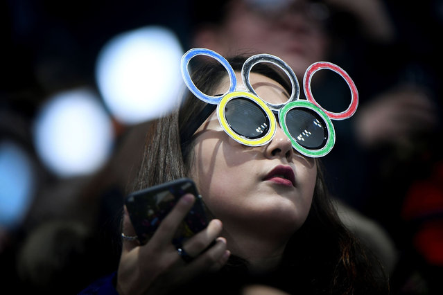 A fan wearing a mask watches the curling men's round robin session between South Korea and Switzerland during the Pyeongchang 2018 Winter Olympic Games at the Gangneung Curling Centre in Gangneung on February 20, 2018. (Photo by Wang Zhao/AFP Photo)