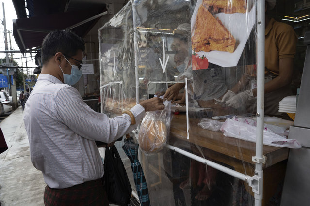 A man wearing a face mask receives take-away food handed over from behind a plastic sheet at a restaurant in Yangon, Myanmar,Monday, September 21, 2020. (Photo by Pyae Sone Win/AP Photo)