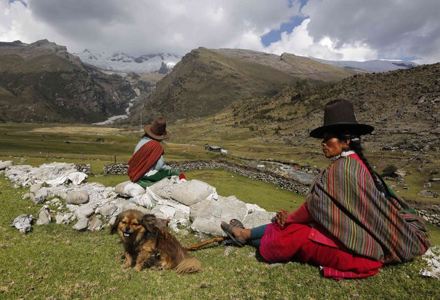 Shepherdess Narcisa Cornelio (R) and her daughter Nancy Condor rest in front of Hualcan glacier in Huascaran natural reserve in Ancash, November 29, 2014. (Photo by Mariana Bazo/Reuters)