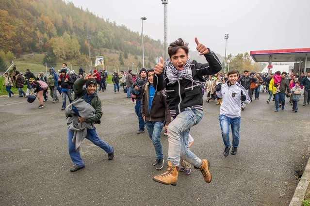 Migrants run to cross the Slovenian-Austrian border on October 29, 2015 from Sentilj. European Commission President Jean-Claude Juncker and Austrian Chancellor Werner Faymann warned on October 28 that fences were not welcome in the EU, after Vienna suggested it could build a barrier on its border with Slovenia to control an influx of migrants. (Photo by Rene Gomolj/AFP Photo)