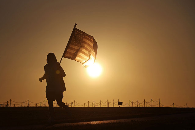 A man carries a U.S. flag as he jogs through the Washington Monument grounds at sunset in Washington, U.S. October 22, 2020. (Photo by Hannah McKay/Reuters)