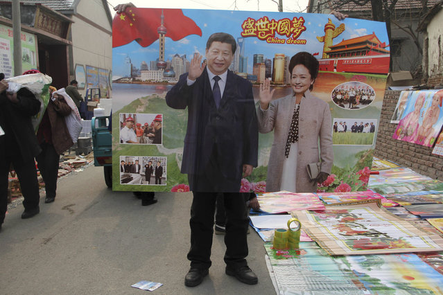 In this January 28, 2016, photo, a vendor holds up a poster of Chinese President Xi Jinping and First Lady Peng Liyuan in a rural market during Chinese New Year season when locals traditionally paste new posters on the walls of their home in Binzhou in eastern China's Shandong province. (Photo by Chinatopix via AP Photo)