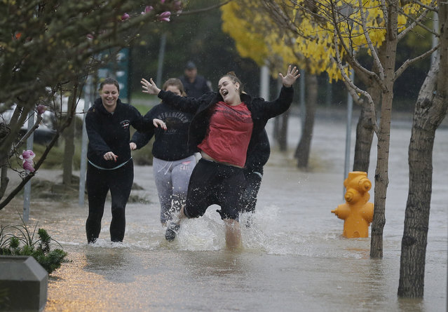 A group of girls laugh while running down a flooded street Thursday, December 11, 2014, in Healdsburg, Calif.  A powerful storm churned through Northern California Thursday, knocking out power to tens of thousands and delaying commuters while soaking the region with much-needed rain. (Photo by Eric Risberg/AP Photo)