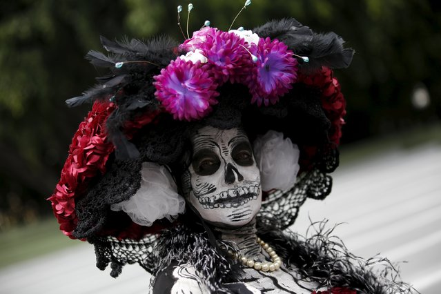 "A woman with her face painted to look like the popular Mexican figure called ""Catrina"", poses for a photograph as she takes part in the annual Catrina Fest in Mexico City November 1, 2015. (Photo by Carlos Jasso/Reuters)"