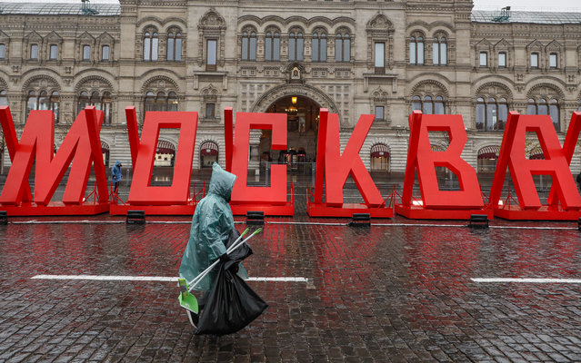 """A municipal worker walks past a sign reading """"Moscow"""" at the exhibition dedicated to the 79th anniversary of the 1941 Red Square Parade and the battle for Moscow during WWII,in Moscow, Russia, 08 November 2020. The exhibition features WWII military hardware and installations of the scene of daily life of Moscow during the war. (Photo by Sergei Ilnitsky/EPA/EFE)"""