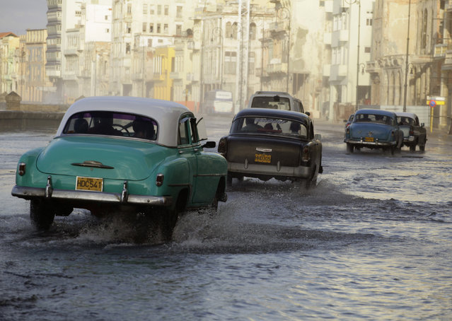 "Cars are driven on Havana's flooded seafront boulevard ""El Malecon"" as a cold front rolls over Havana, November 5, 2010. (Photo by Desmond Boylan/Reuters)"
