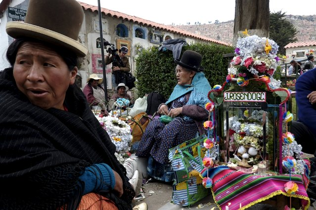 """Aymara women sit near skulls placed on the floor during a ceremony held for the """"Dia de las natitas"""" (Day of the Skull) celebrations at the General Cemetery of La Paz, November 8, 2015. (Photo by David Mercado/Reuters)"""