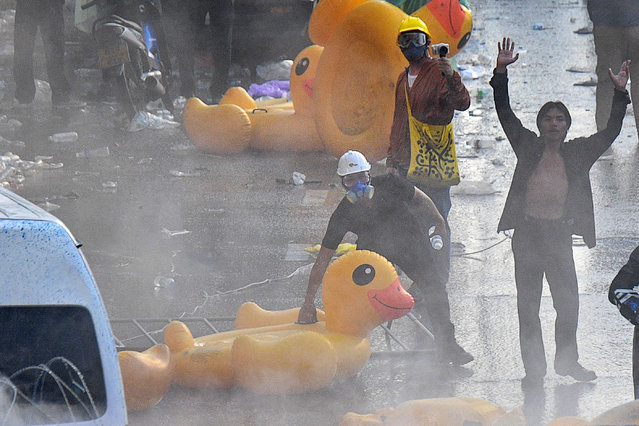 Protesters stand with oversized inflatable rubber ducks in front of police water cannon trucks during an anti-government rally in Bangkok on November 17, 2020. (Photo by Mladen Antonov/AFP Photo)