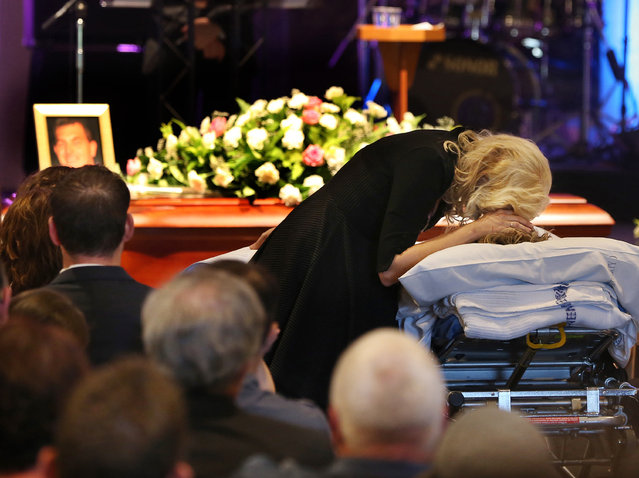 """It's a heartbreaking and rare sight – a son wheeled in on a stretcher bed to his father's funeral"", said the awards team. ""The service was delayed so that 17-year-old Brendan Powell could attend from hospital after being injured in a crane collapse at Newstead that killed his father, aerial photographer Chris Powell. (This shot) captured a family's loss and grief. The family revealed that his final, heartbreaking words to Brendan were: ""Close your eyes, I love you"". (Photo by Annette Dew/The Walkley Foundation)"