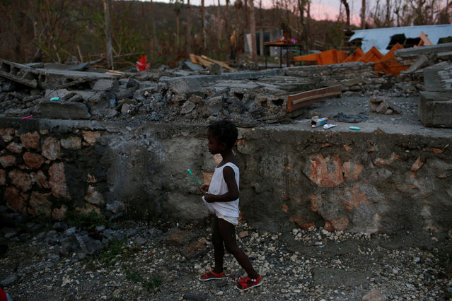 A girl walks next to a partially destroyed school used as a shelter after Hurricane Matthew hit Jeremie, Haiti, October 15, 2016. (Photo by Carlos Garcia Rawlins/Reuters)