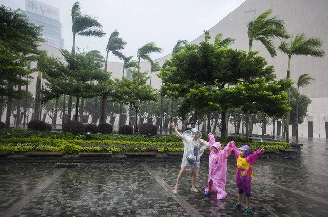 People walk through gale-force winds as Typhoon Haima makes landfall on the South China coast, in Hong Kong, China, 21 October 2016. (Photo by Alex Hofford/EPA)