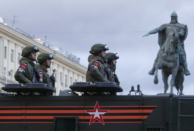 Russian servicemen are seen onboard a military vehicle in Tverskaya Street near the monument to Prince Yuri Dolgoruky before the rehearsal for the Victory Day parade in central Moscow, Russia April 26, 2018. (Photo by Tatyana Makeyeva/Reuters)