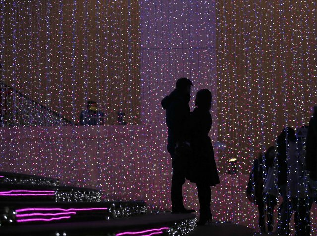 A couple hug each other in front of a light installation for Christmas celebrations in Beijing December 23, 2014. (Photo by Kim Kyung-Hoon/Reuters)