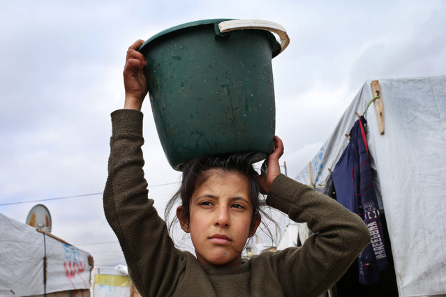 A Syrian girl carries water on her head at a refugee camp, in Deir Zannoun village, Bekaa valley, Lebanon, Tuesday, January 6, 2015. (Photo by Hussein Malla/AP Photo)
